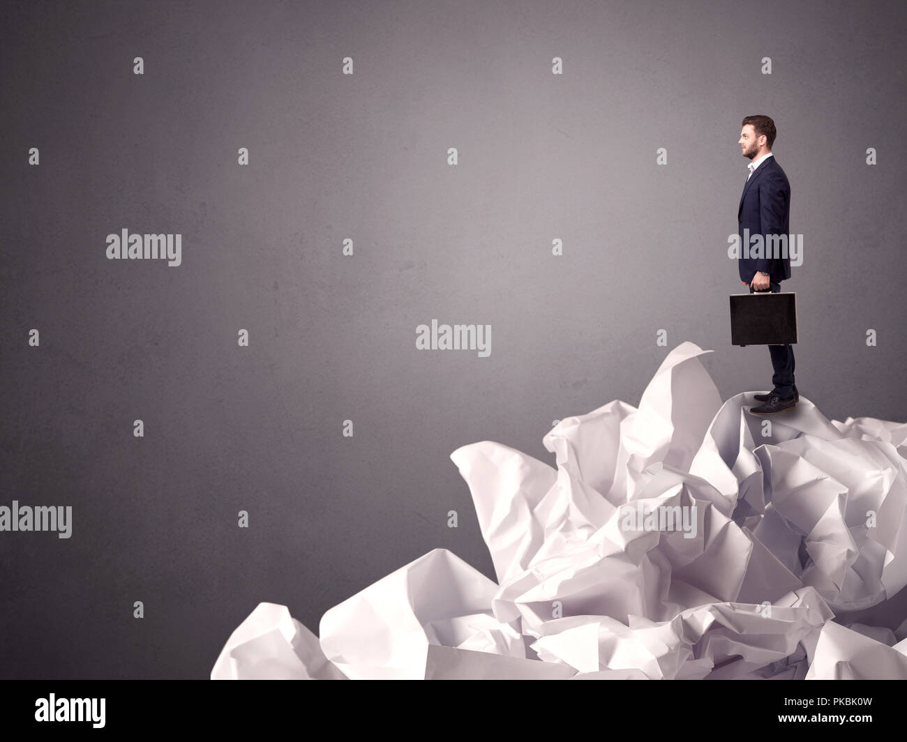 Thoughtful young businessman standing on a pile of crumpled paper with a grungy grey background Stock Photo