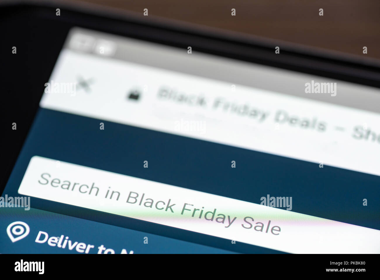 Black Friday Sale text in search box on shopping app on smartphone screen closeup. - Stock Image