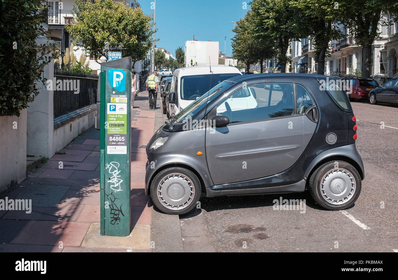 Smart car parked sideways in small space on street in Brighton UK - Stock Image