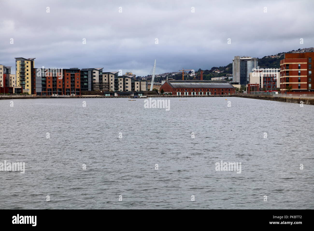 The Prince of Wales Doc now surrounded on three sides by new build flats with a wharehouse at the far end situated on the outskirts of Swansea. - Stock Image