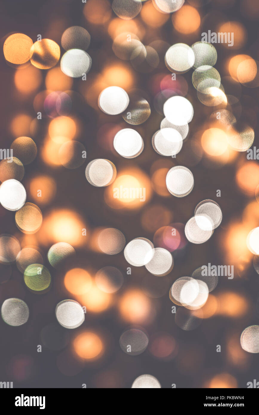 Retro bokeh lights on a dark background with glittering blurs in various colors - Stock Image