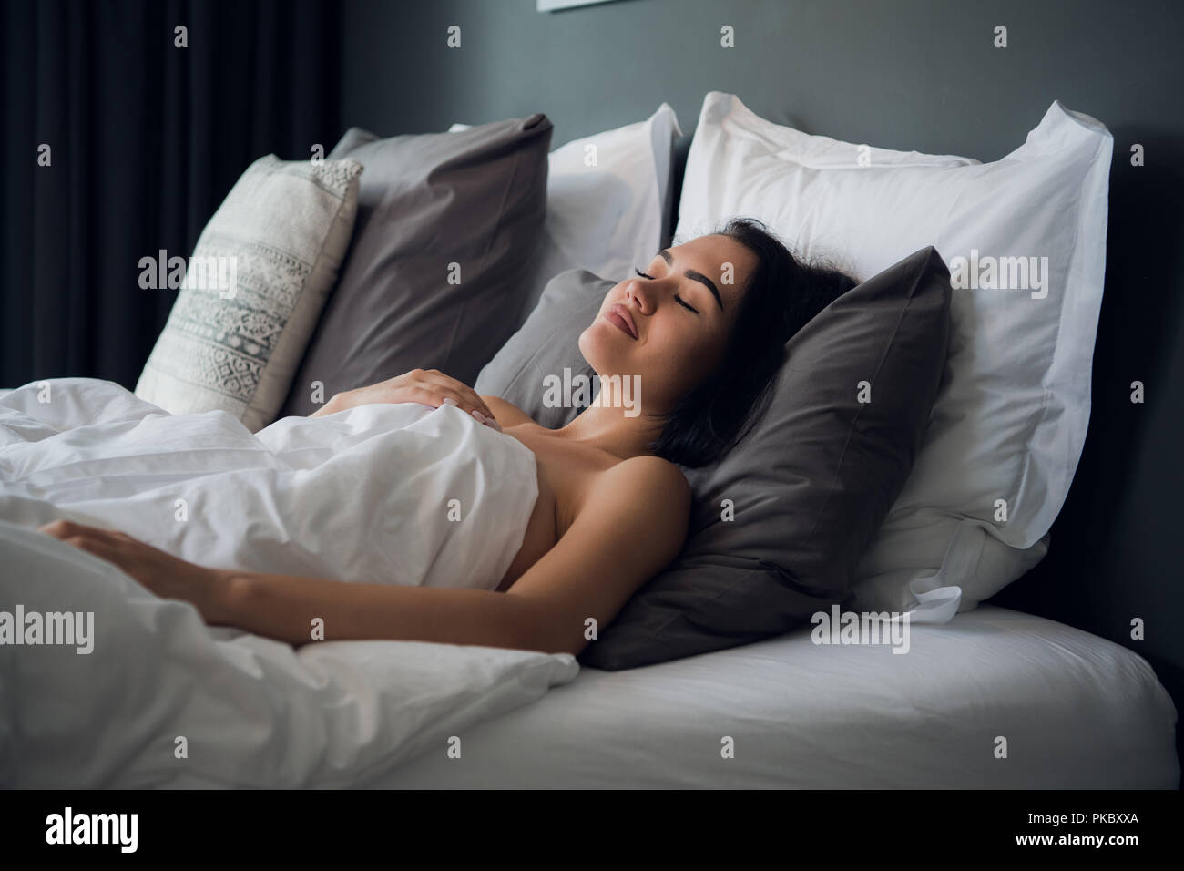 night, rest, comfort and people concept - young woman sleeping in bed at home - Stock Image