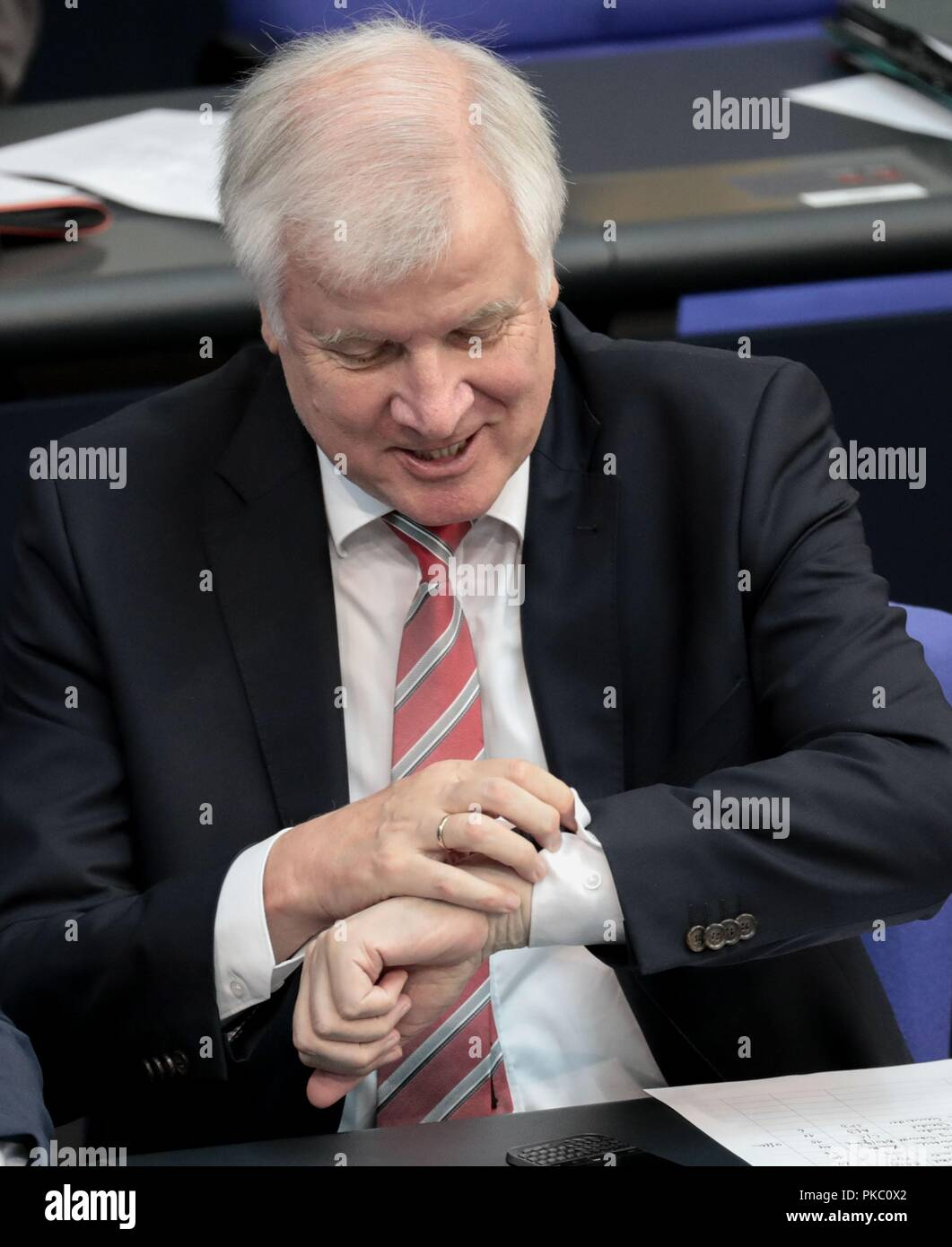 Berlin, Germany. 12th Sep, 2018. Horst Seehofer (CSU), Federal Minister of the Interior, for Building and Home, looks at the clock during the general debate in the German Bundestag. The main topic of the 48th session of the 19th legislative period is the draft of the Federal Budget 2019 submitted by the Federal Government and the Federal Finance Plan 2018 to 2022 with the general debate on the budget of the Federal Chancellery. Credit: dpa picture alliance/Alamy Live News - Stock Image