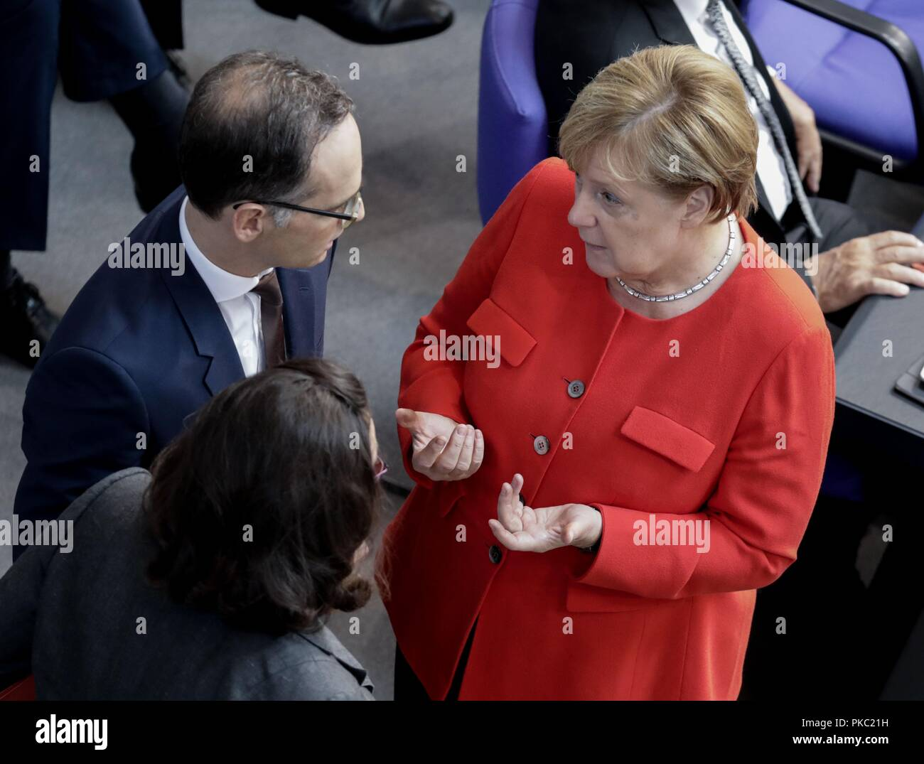 Berlin, Germany. 12th Sep, 2018. Chancellor Angela Merkel (CDU) will address the general debate in the German Bundestag with Andrea Nahles (M), SPD faction leader and SPD party leader, and Heiko Maas (l, SPD), Foreign Minister. The main topic of the 48th session of the 19th legislative period is the draft of the Federal Budget 2019 submitted by the Federal Government and the Federal Finance Plan 2018 to 2022 with the general debate on the budget of the Federal Chancellery. Photo: Kay Nietfeld/dpa - Stock Image