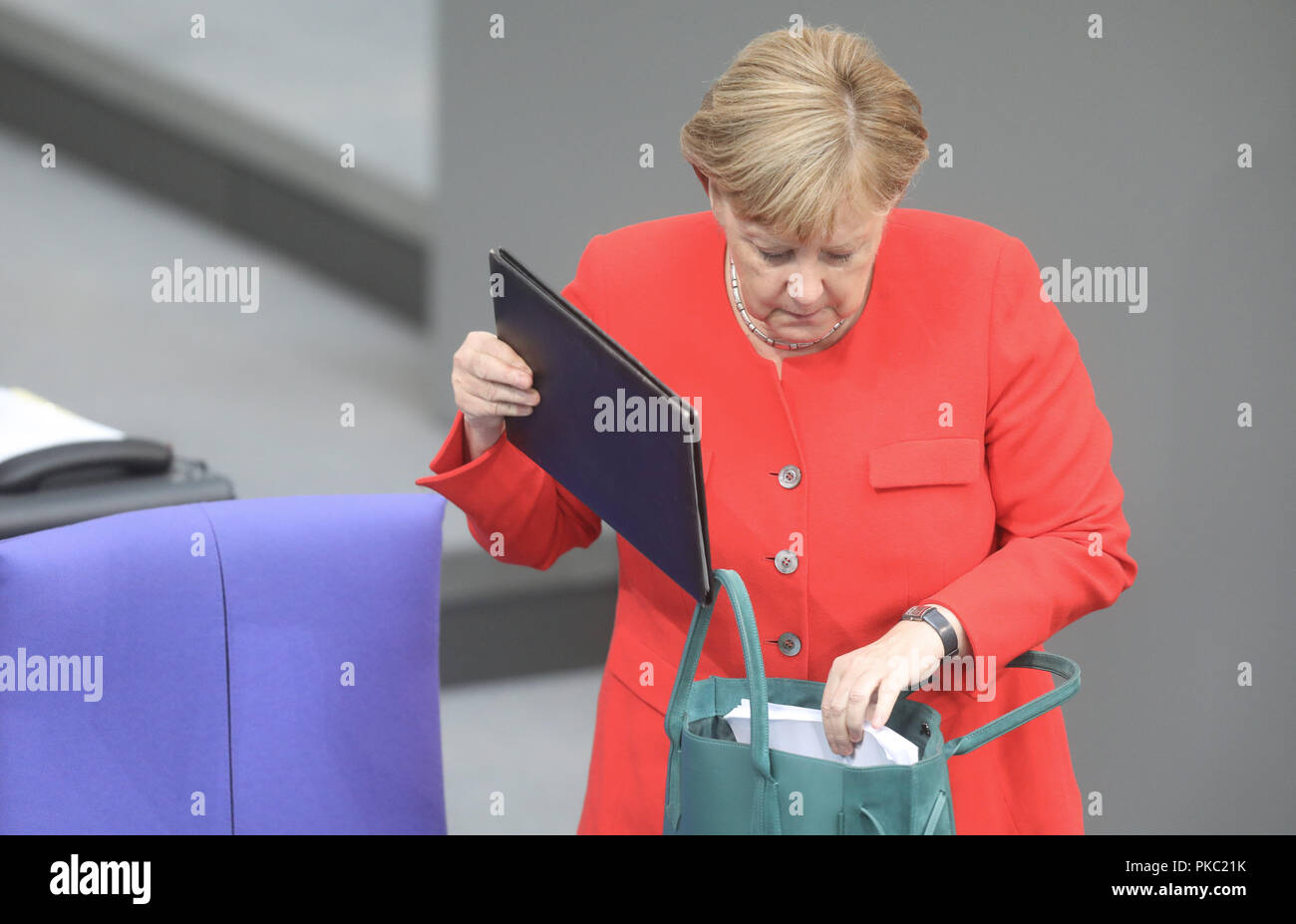 Berlin, Germany. 12th Sep, 2018. Chancellor Angela Merkel (CDU) puts her laptop in her handbag during the general debate in the German Bundestag. The main topic of the 48th session of the 19th legislative period is the draft of the Federal Budget 2019 submitted by the Federal Government and the Federal Finance Plan 2018 to 2022 with the general debate on the budget of the Federal Chancellery. Photo: Jörg Carstensen/dpa - Stock Image
