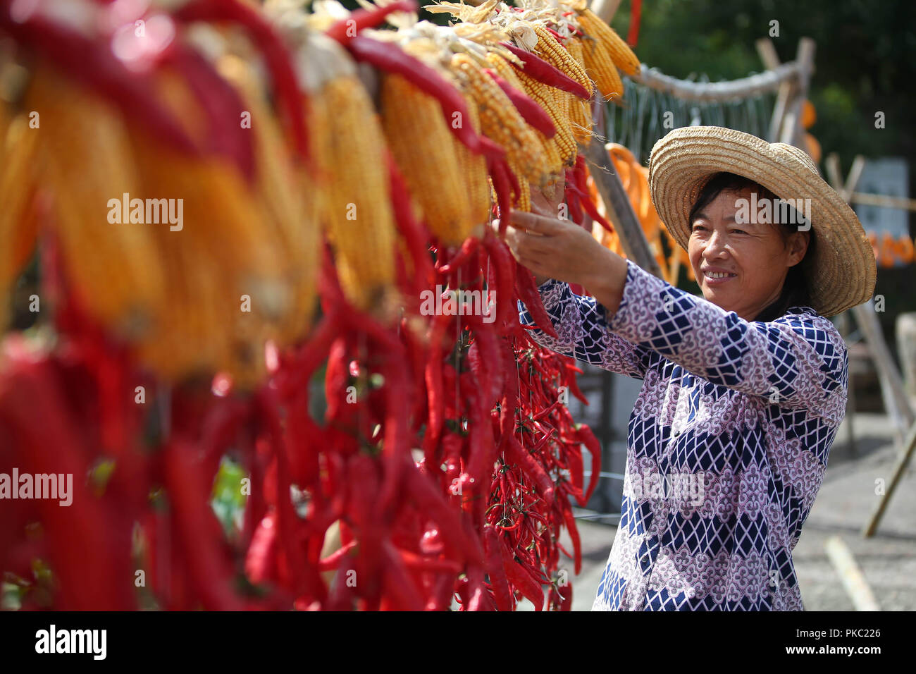Huangshan, China's Anhui Province. 12th Sep, 2018. A villager airs chillies and corns at Chengkan Ancient Village in the city of Huangshan, east China's Anhui Province, on Sept. 12, 2018. Credit: Shi Yalei/Xinhua/Alamy Live News - Stock Image