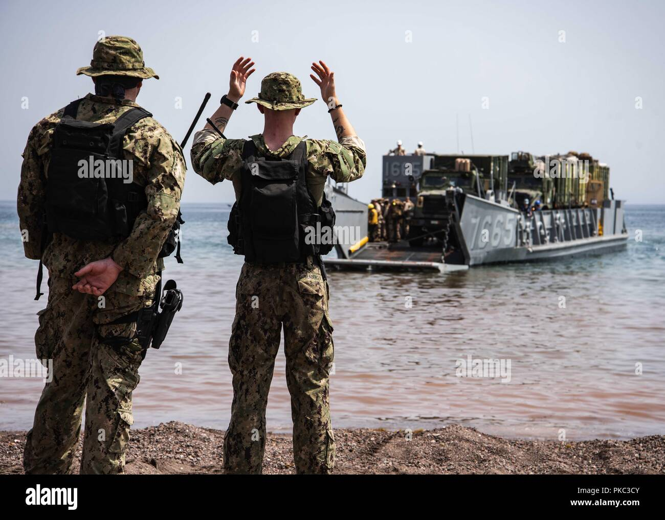Djibouti. 8th Mar, 2018. DJIBOUTI (Sept. 8, 2018) Engineman Fireman Cory Durenberger, assigned to Beach Master Unit (BMU) 1, signals a landing craft utility while participating in Theater Amphibious Combat Rehearsal (TACR) 18. Led by Naval Amphibious Force, Task Force 51/5th Marine Expeditionary Brigade, TACR integrates U.S. Navy and Marine Corps assets to practice and rehearse a range of critical combat-related capabilities available to U.S. Central Command, both afloat and ashore, to promote stability and security in the region. U.S. 5th Fleet and coalition assets are participating in nume Stock Photo