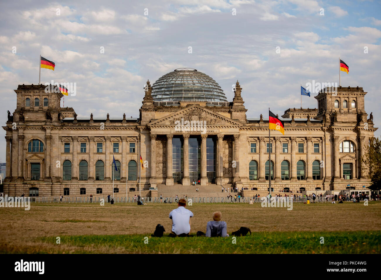 12 September 2018, Berlin: 12 September 2018, Germany, Berlin: Two men are lying on the meadow in front of the Reichstag building. Photo: Christoph Soeder/dpa - Stock Image