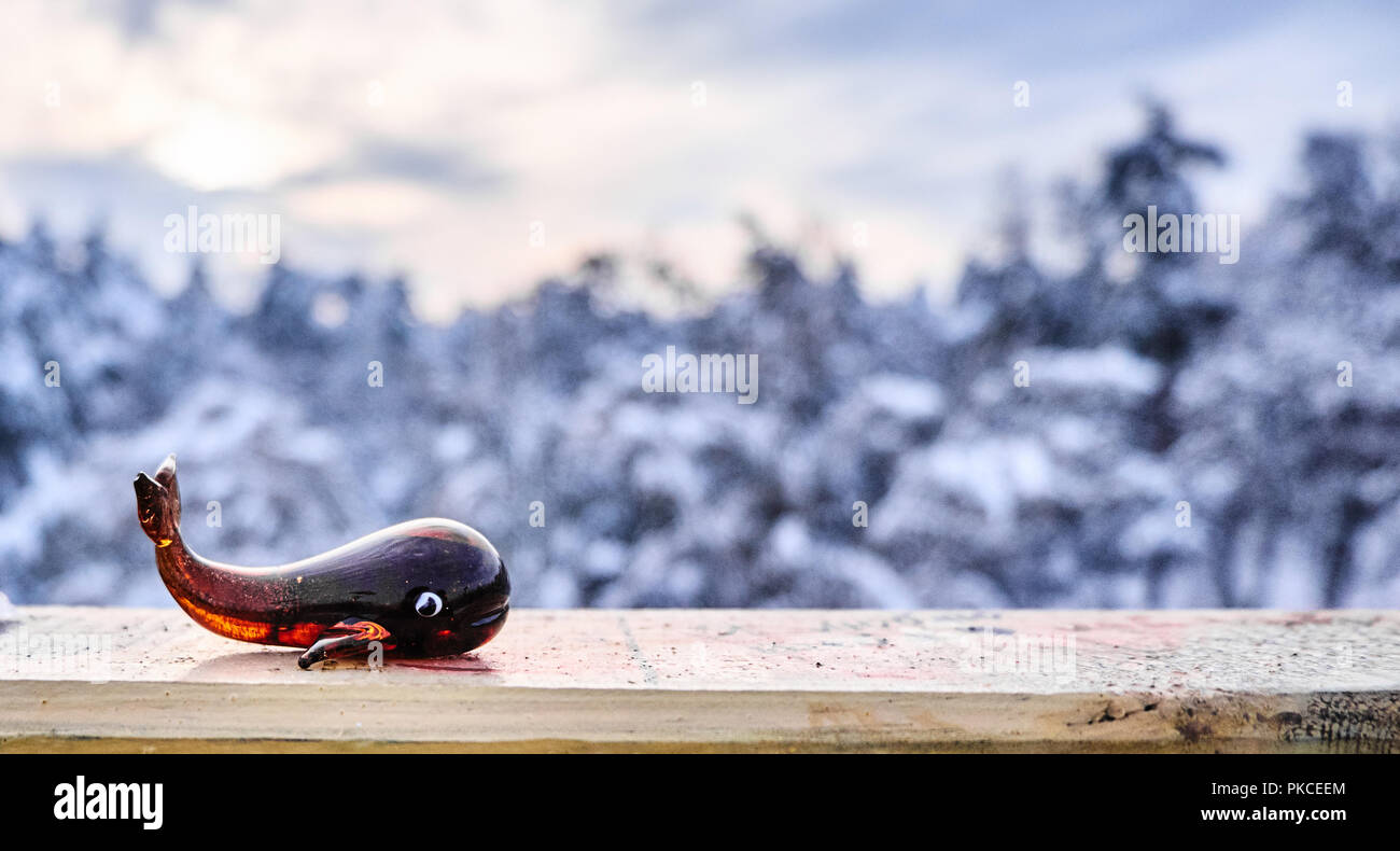 Winter background. Glass whale toy in front of forest covered with snow - Stock Image