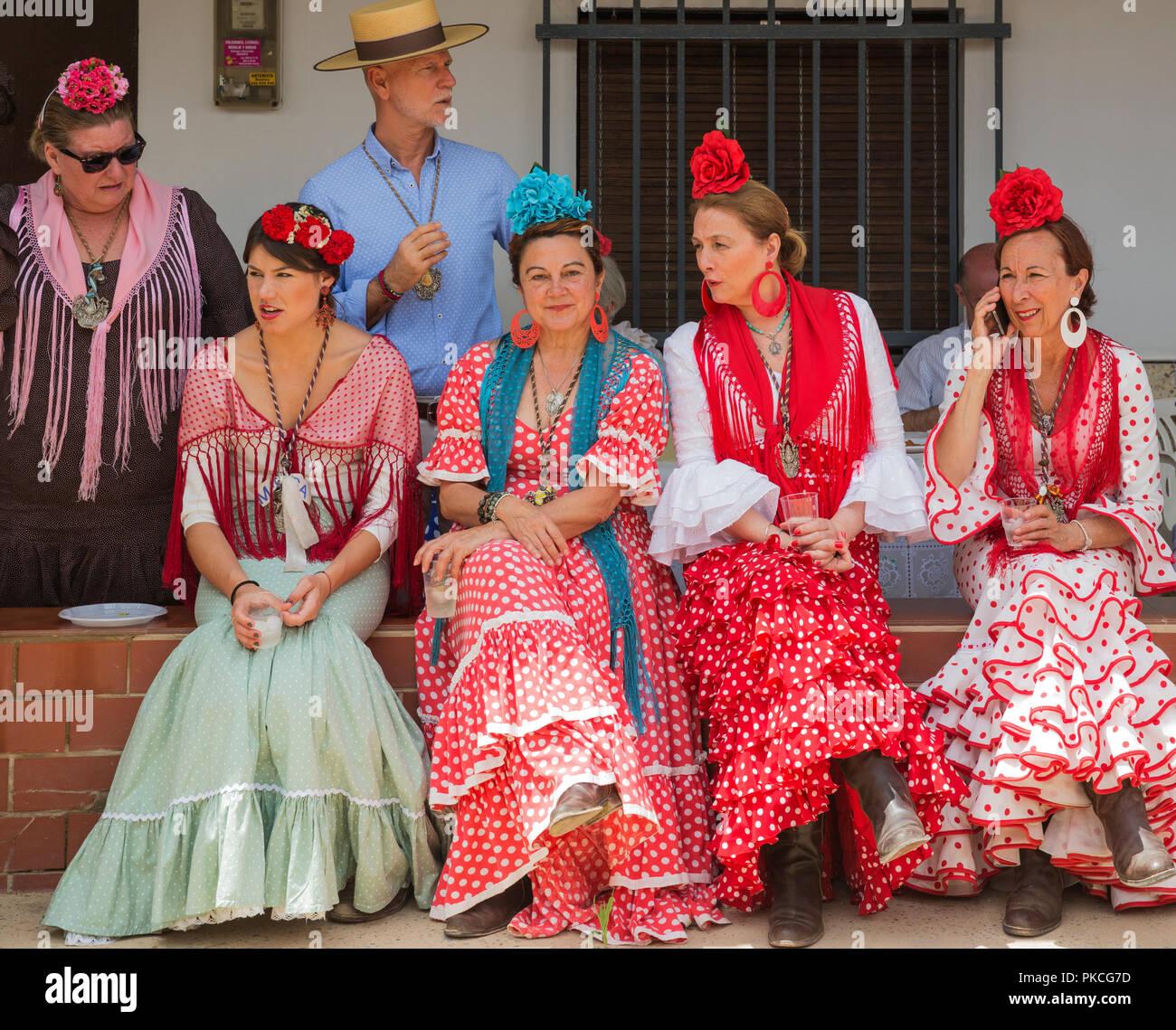 Women wearing colourful gypsy dresses, Pentecost pilgrimage of El Rocio, Huelva province, Andalusia, Spain - Stock Image