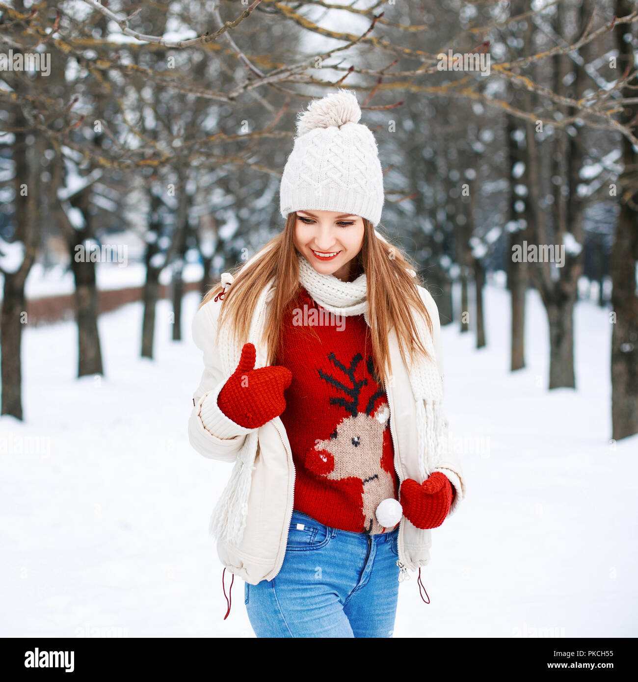 Lovely girl with a stylish retro sweater, a white winter jacket and knit cap  looking down on the background of the park