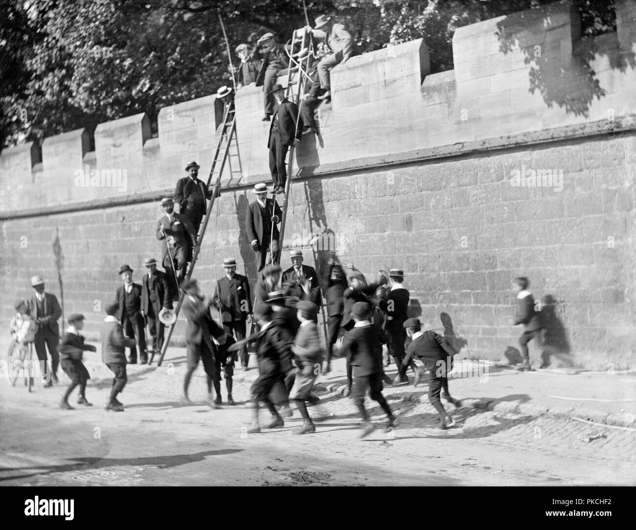 Beating the Bounds, Longwall Street, Oxford, Oxfordshire, 1908. Boys scramble for coins at Longwall during the annual ceremony of beating the bounds, which reinforces knowledge of the parish boundary. The ceremony, which takes place on Ascension Day, is led by the parish priest, seen here up the ladder. - Stock Image