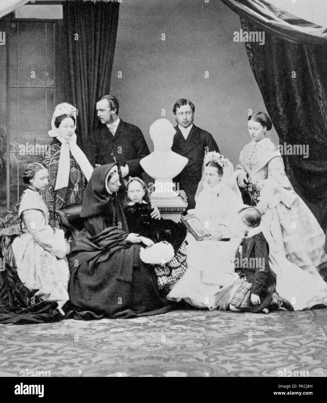 Queen Victoria and her family, Windsor, Berkshire, 1863. Photograph from a Royal Familty album at Osborne House, Isle of Wight, possibly taken at the time of the Prince of Wales' marriage. The family are arranged around a bust of Albert, the late Prince Consort.  Standing (left to right): possibly Crown Princess of Prussia (1840-1901); Grand Duke Louis of Hesse (1837-1892); Prince Albert Edward, Prince of Wales (1841-1910); Princess Helena (1846-1923). In front (left to right): Princess Alice (1843-1878); Queen Victoria (1819-1901); Princess Beatrice (1857-1944); Princess Alexandra of Denmark, Stock Photo