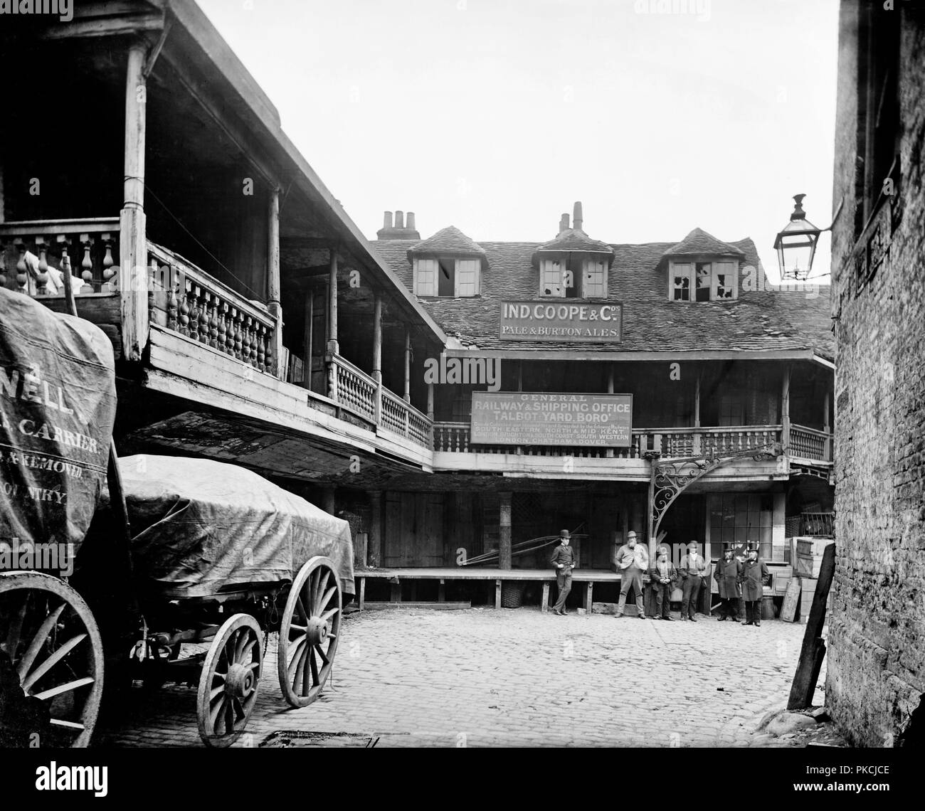 Tabard or Talbot Inn, Talbot Yard, Southwark, London, c1870-c1873. A view of the courtyard with a wagon in the foreground and a group of people. The Tabard was an established inn during the Middle Ages and features in Chaucer's The Canterbury Tales, written in the late 14th century. The pilgims met here before setting out on their journey to Canterbury Cathedral. The inn burnt down in 1676 and it is the rebuilt one (which may be based on the original building) that is pictured here. As a coaching inn it suffered from the coming of the railways. Renamed the Talbot Inn, the buildings around the  - Stock Image