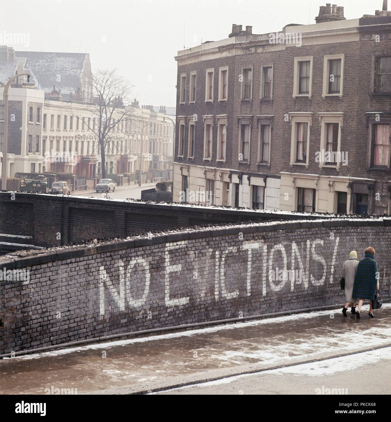 Two women walking past the graffiti no evictions on a railway bridge on grafton road much of the area was bulldozed and redeveloped in the 1960s and