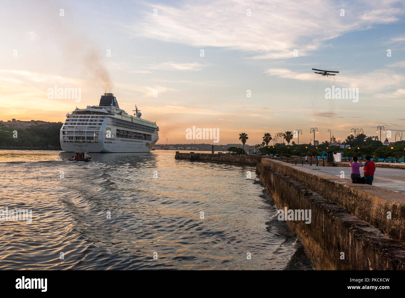 Havana, Cuba. 04th July 2017. Cruise liner Norwegian Sky makes her way up to her dock escorted by the pilot boat while an old vintage biplane flies ov - Stock Image