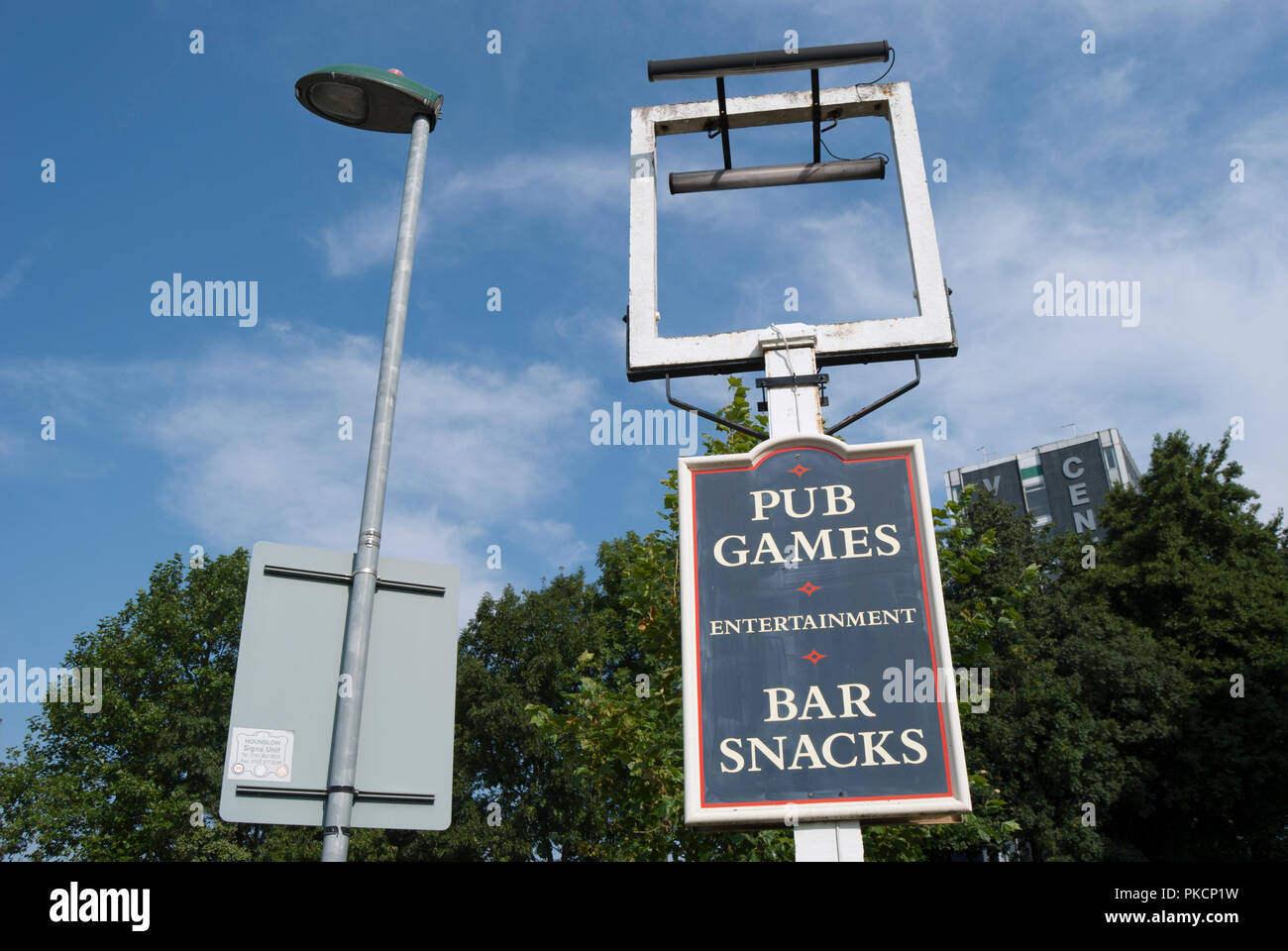 empty frame for a pub sign above pub games and bar snacks sign, and rear side of road sign in hounslow, middlesex, england - Stock Image