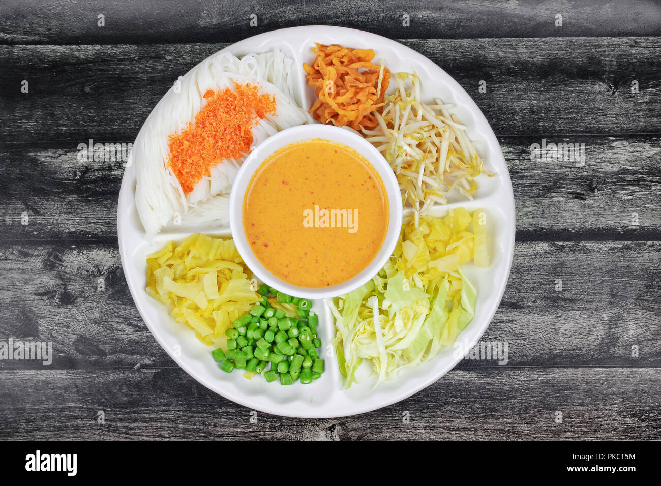Rice noodle topped minced dried shrimp served with fish curry in coconut milk and herb as minced pickle lettuce,sliced cabbage ,Sprouts, Radish and lo - Stock Image