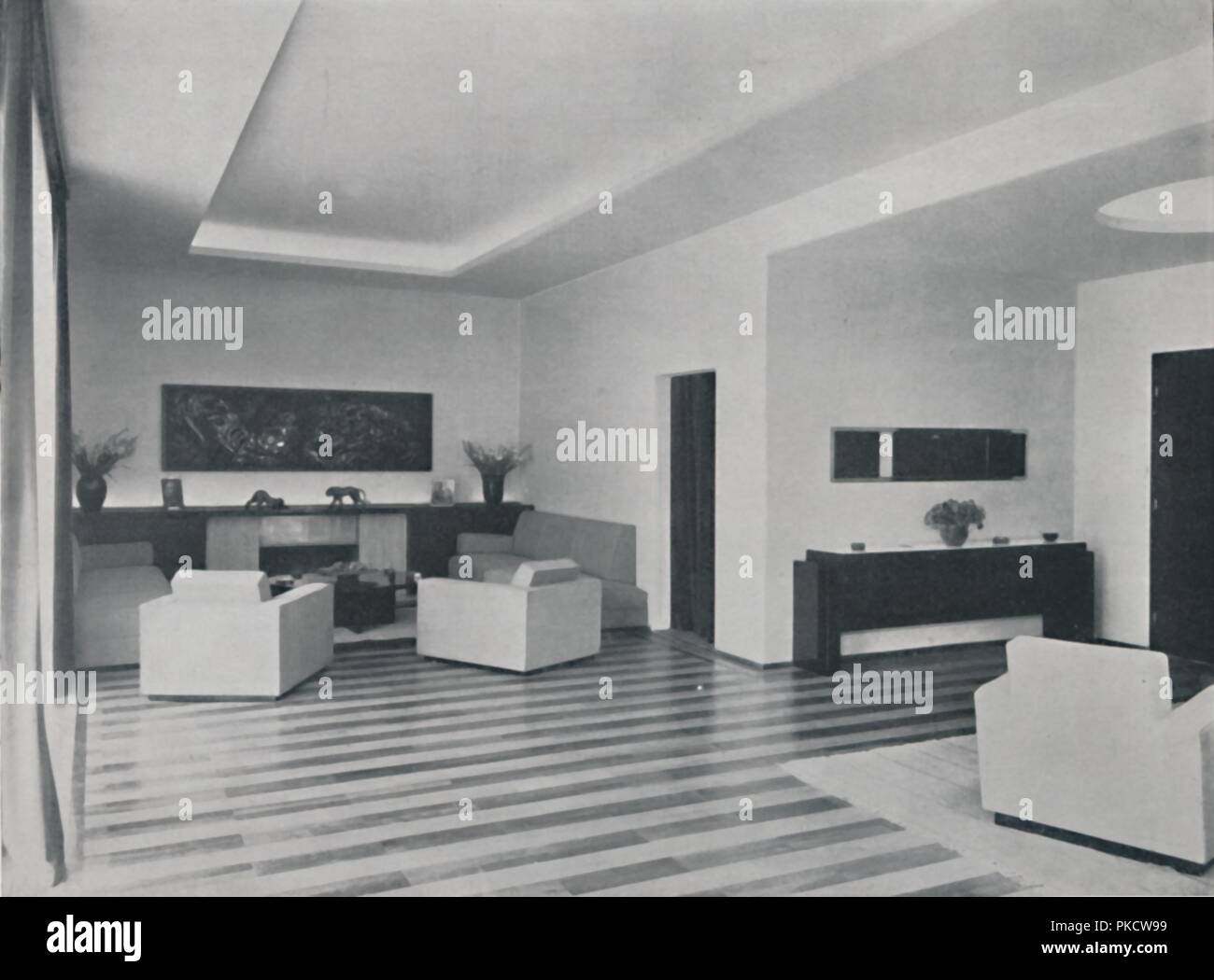 'House in Bucharest by Rudolf Frankel - The sitting room', 1942. The sitting room and dining room form a single large living space divided by curtains. The sitting corner has an open, bronze-hooded fireplace in travertine and black marble with a wood carving above. Fittings and furniture of dark walnut. From Decorative Art 1942 - The Studio Year Book, edited by C. G. Holme. [The Studio Ltd., London, 1942] - Stock Image