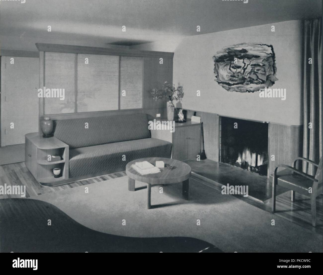 'House at Pomona, California - the living room from the other side of the partition', 1942. Vignette above fireplace is a fresco by Milford Zornes, painted on wet plaster. Furniture, fabrics and colour scheme designed by Honor Easton and Alyne Whalen. From Decorative Art 1942 - The Studio Year Book, edited by C. G. Holme. [The Studio Ltd., London, 1942] - Stock Image