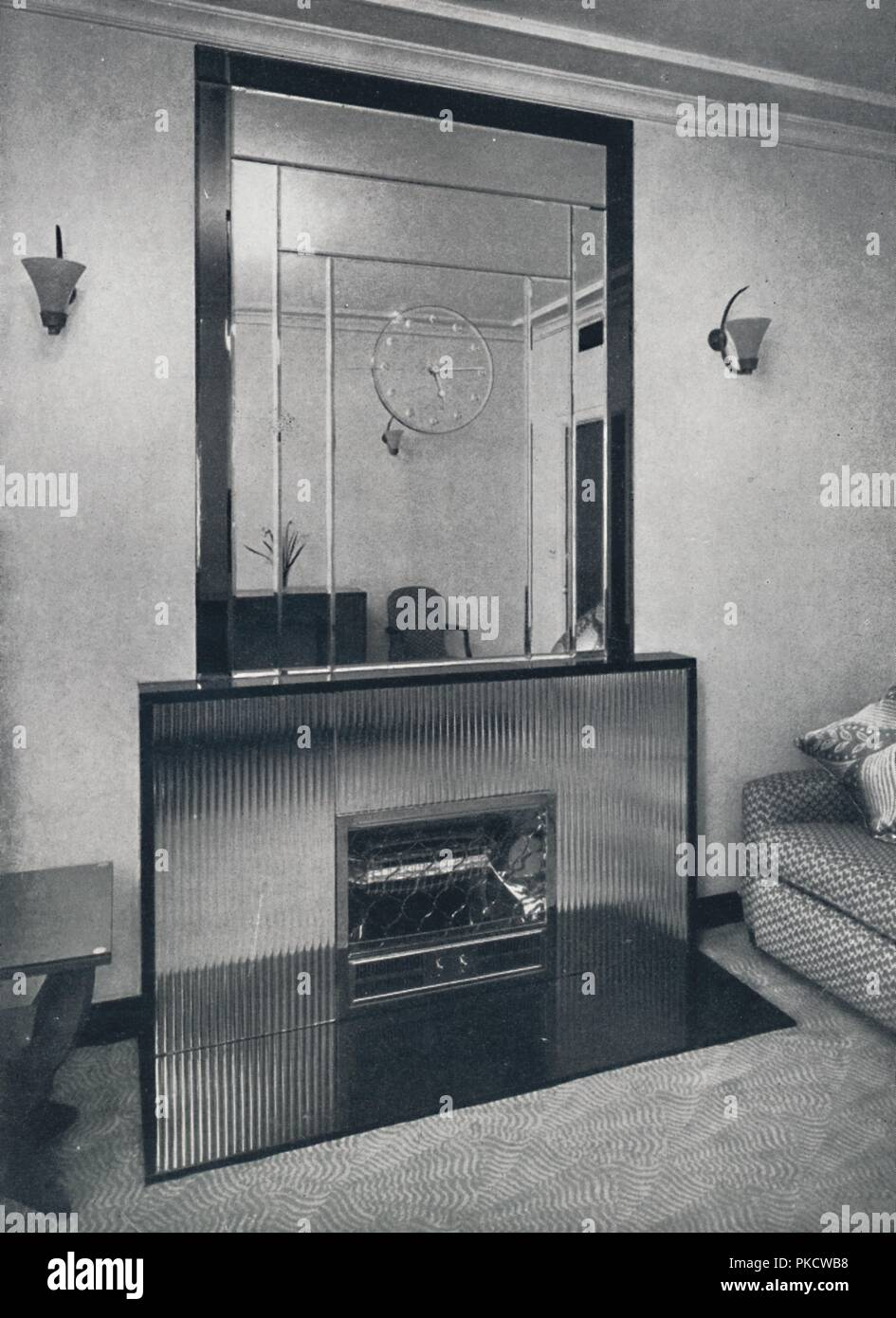 'W. Curtis Green, R.A. - Electric fireplace and overmantel by James Clark & Son Ltd.', 1940. Overmantel is of 3/4 inch bevelled section mirror glass bordered by a Neutral tint mirror, withe brilliant-cut mirror clock face superimposed. Fire surround is of 3/4 inch white reeded silvered glass, set into black marble framework and hearth. From 'Decorative Art 1940 - The Studio Year Book, edited by C. G. Holme. [The Studio Ltd., London, 1940] - Stock Image