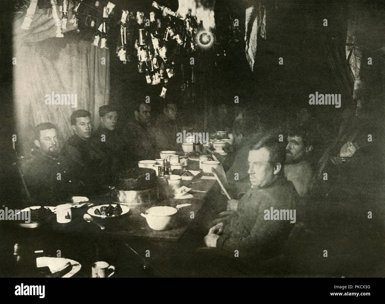 'The Midwinter's Day Feast', June 1908, (1909). The midwinter feast at the Nimrod Hut, Cape Royds. Ernest Shackleton is at the head of the table. On the left side are Armytage, Brocklehurst, Marston, Day, Adams and Marshall; on the right, Roberts, Mackay, Murray, Wild, Joyce, Mawson. Anglo-Irish explorer Ernest Shackleton (1874-1922) made three expeditions to the Antarctic. During the second expedition, 1907-1909, he and three companions established a new record, Farthest South latitude at 88°S, only 97 geographical miles (112 statute miles, or 180 km) from the South Pole, the largest adv - Stock Image
