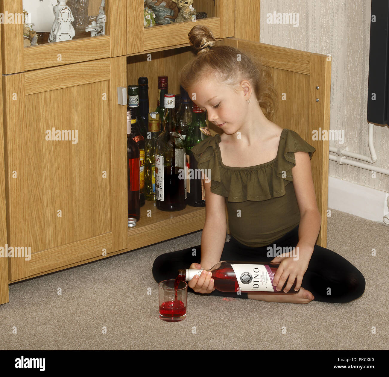A six year old girl helping herself to wine from a drinks cabinet - Stock Image