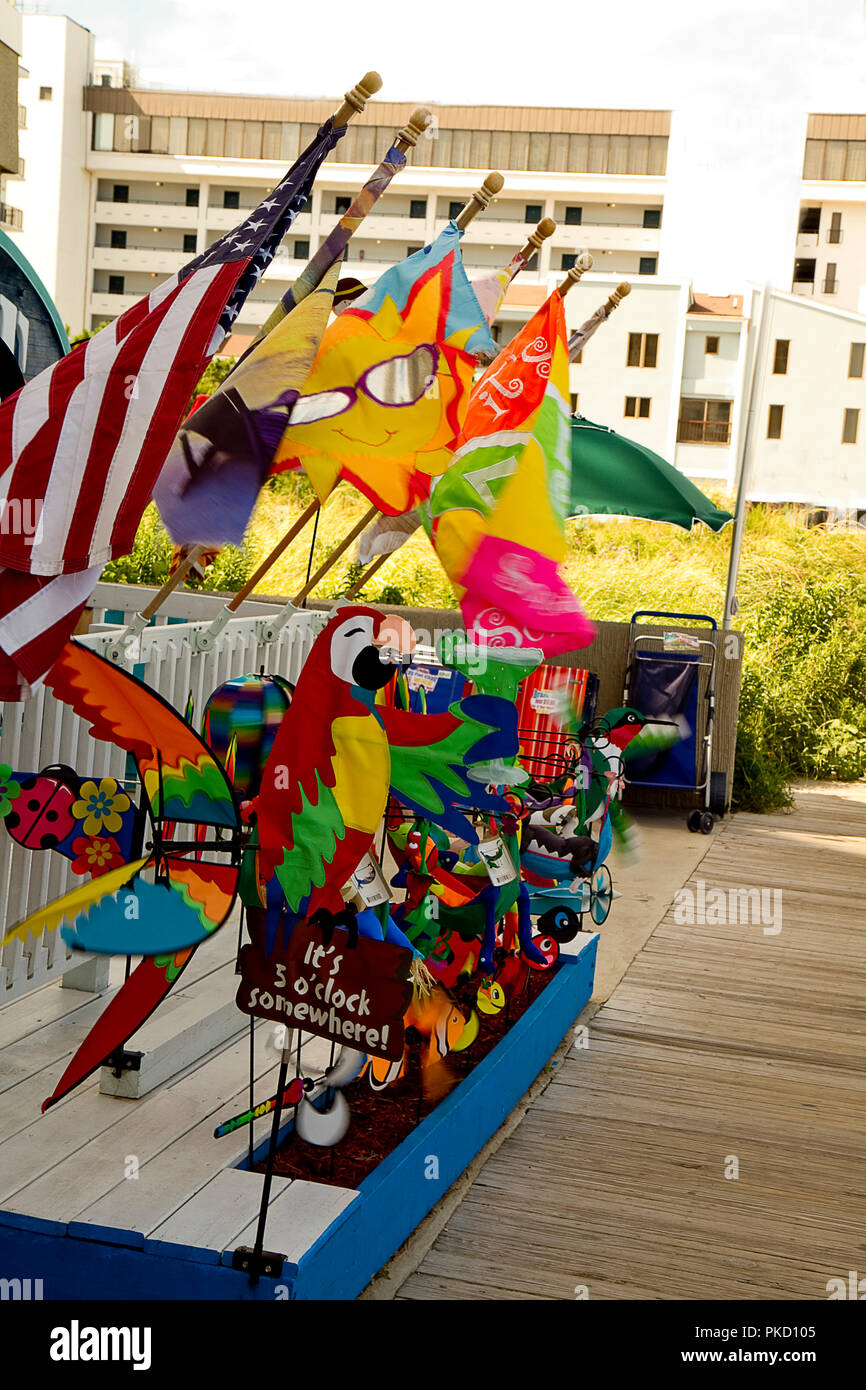 Novelty wind spinners in all different shapes and sizes on stands outside store off boardwalk. - Stock Image