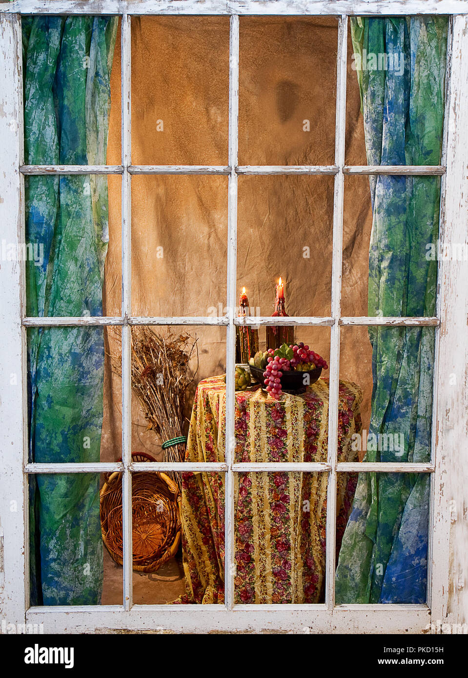View through old weathered window-panes of quaint home with curtains and a round table with a  retro looking tablecloth and candles with dripping wax. - Stock Image