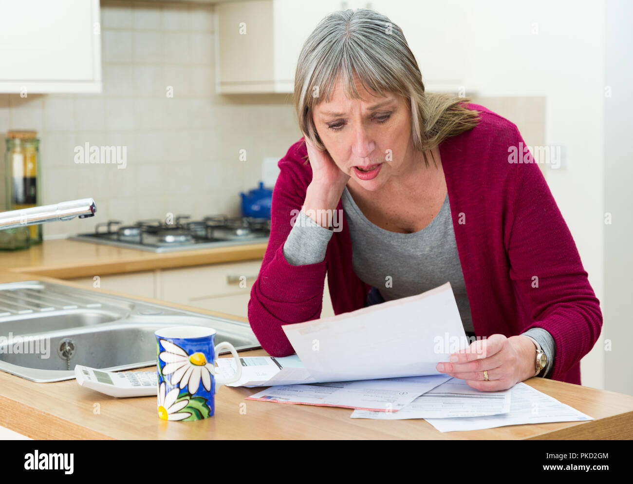 woman shocked by credit card bill / mortgage / loans - Stock Image