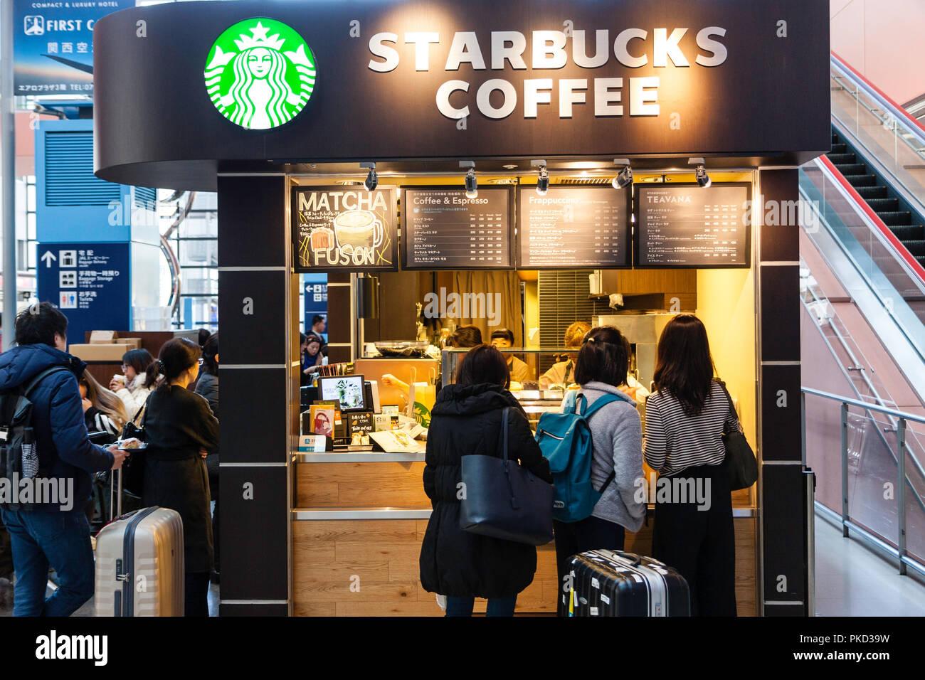 Japan, Osaka. Kansai International Airport. KIX, Interior terminal one, ground floor arrival area. Starbucks coffee shop with people at counter. - Stock Image