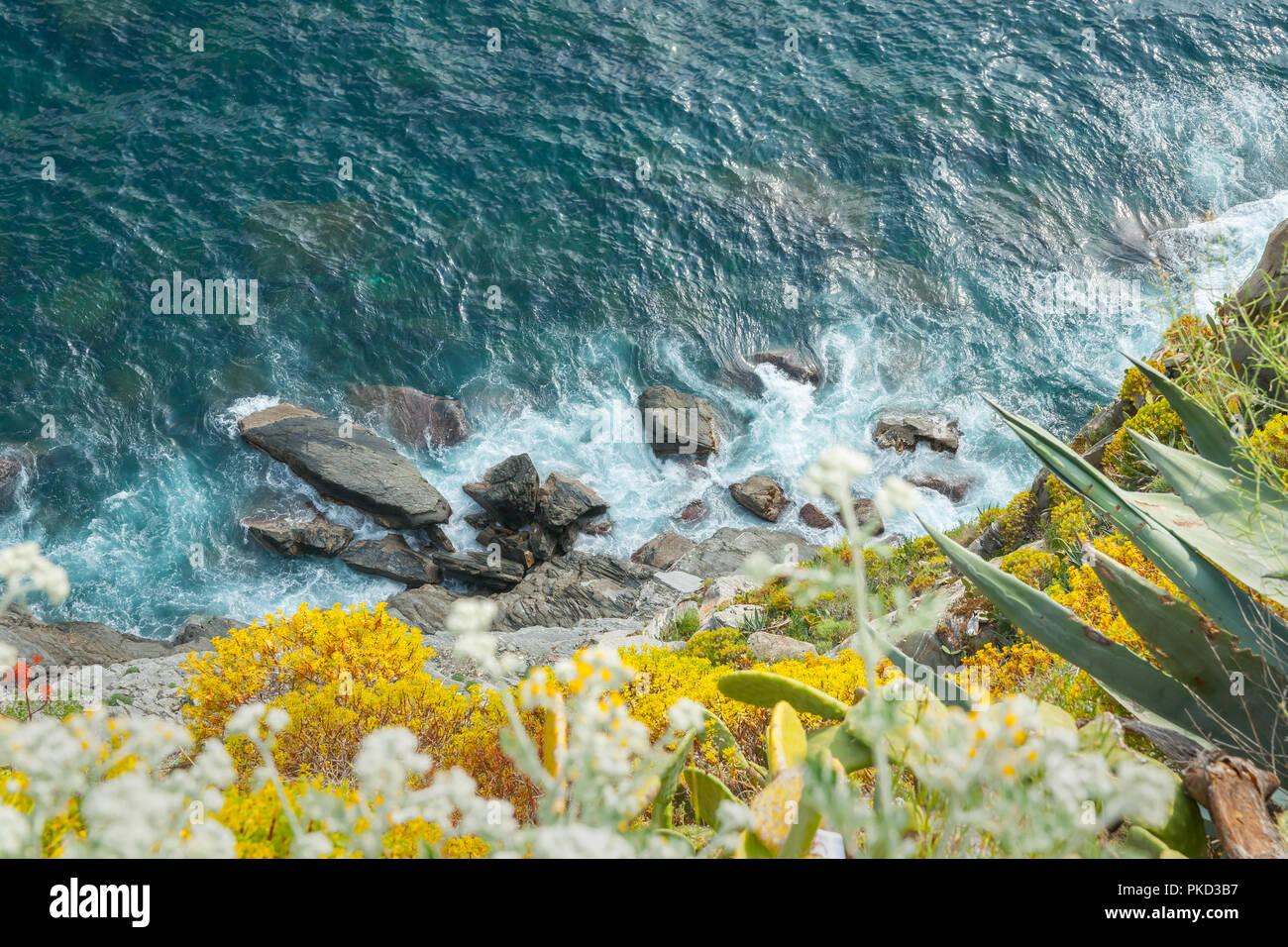 Mediterranean sea crashes onto rocky coastline way down bottom of bank on Italian coastal edge. - Stock Image