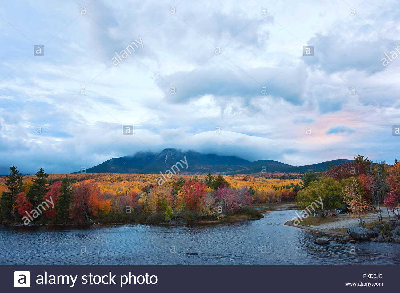mount katahdin surrounded in clouds with bright fall foliage and lake in the foreground - Stock Image
