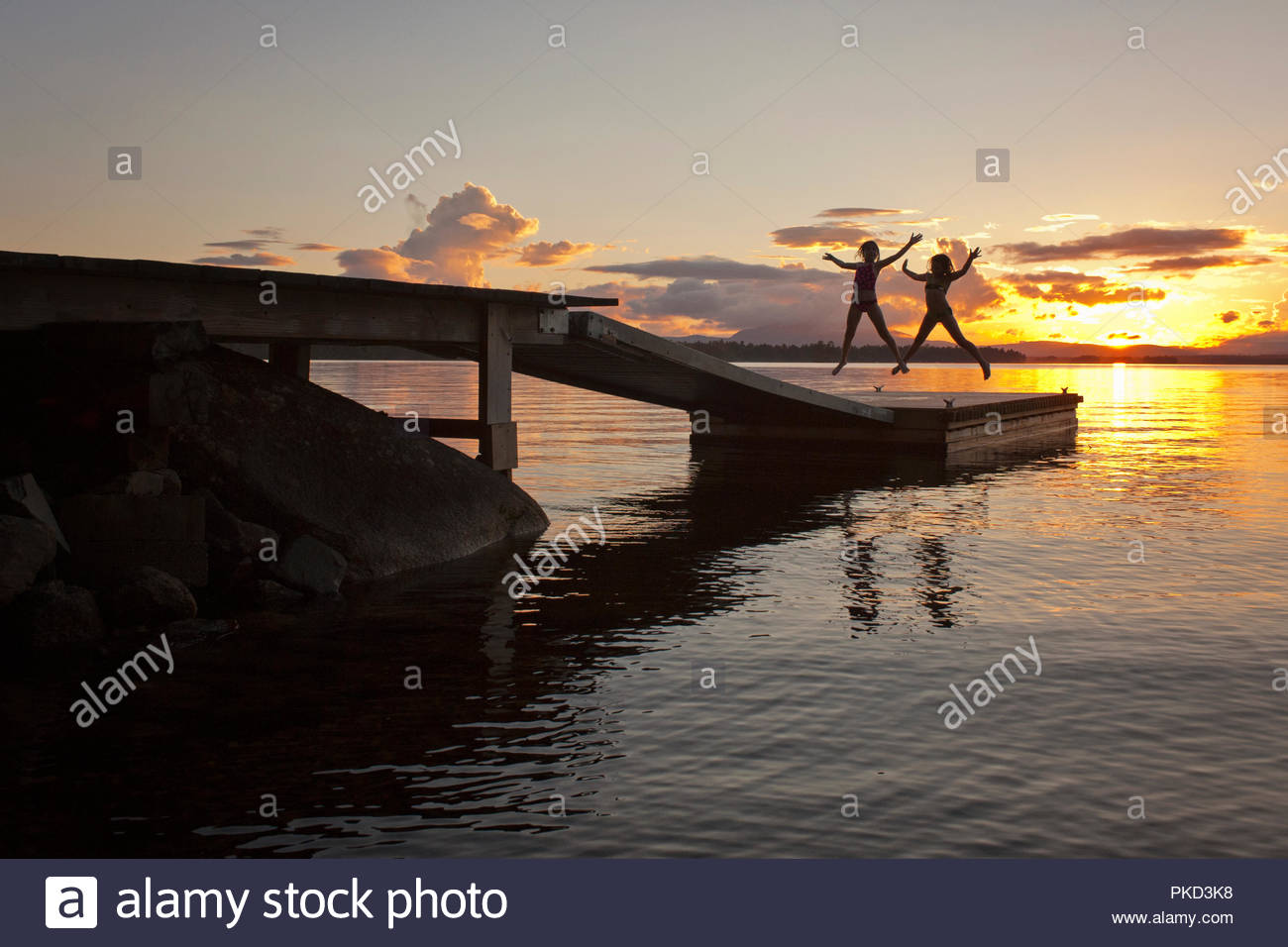 two silhouetted subjects jumping in sync on lake dock at sunset - Stock Image
