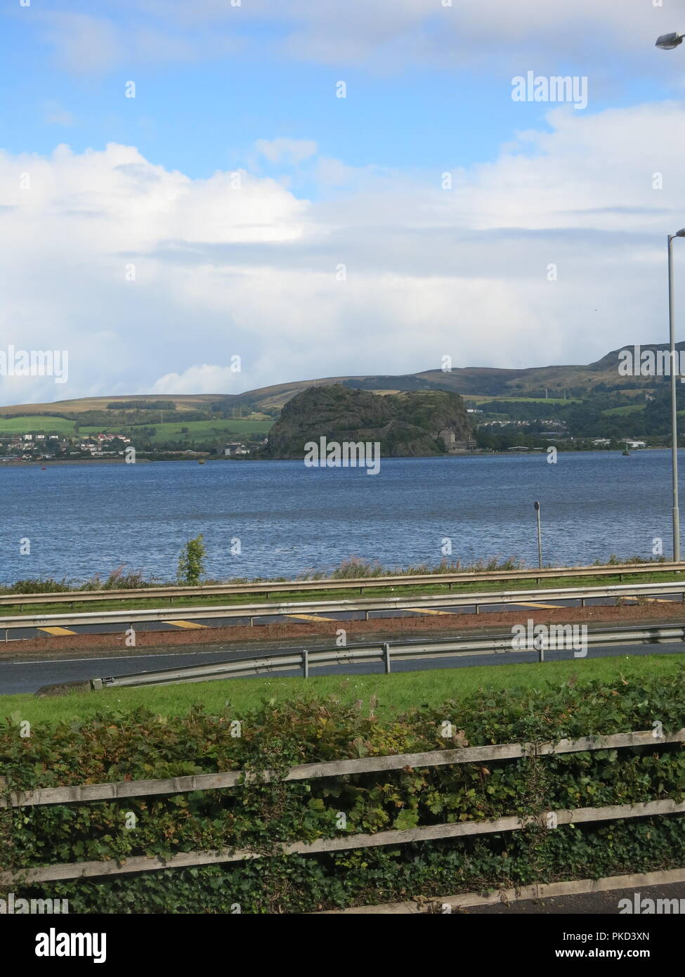A view of Dumbarton Rock from across the Clyde Estuary on the shores of Langbank, Port Glasgow, Scotland (September 2018) - Stock Image