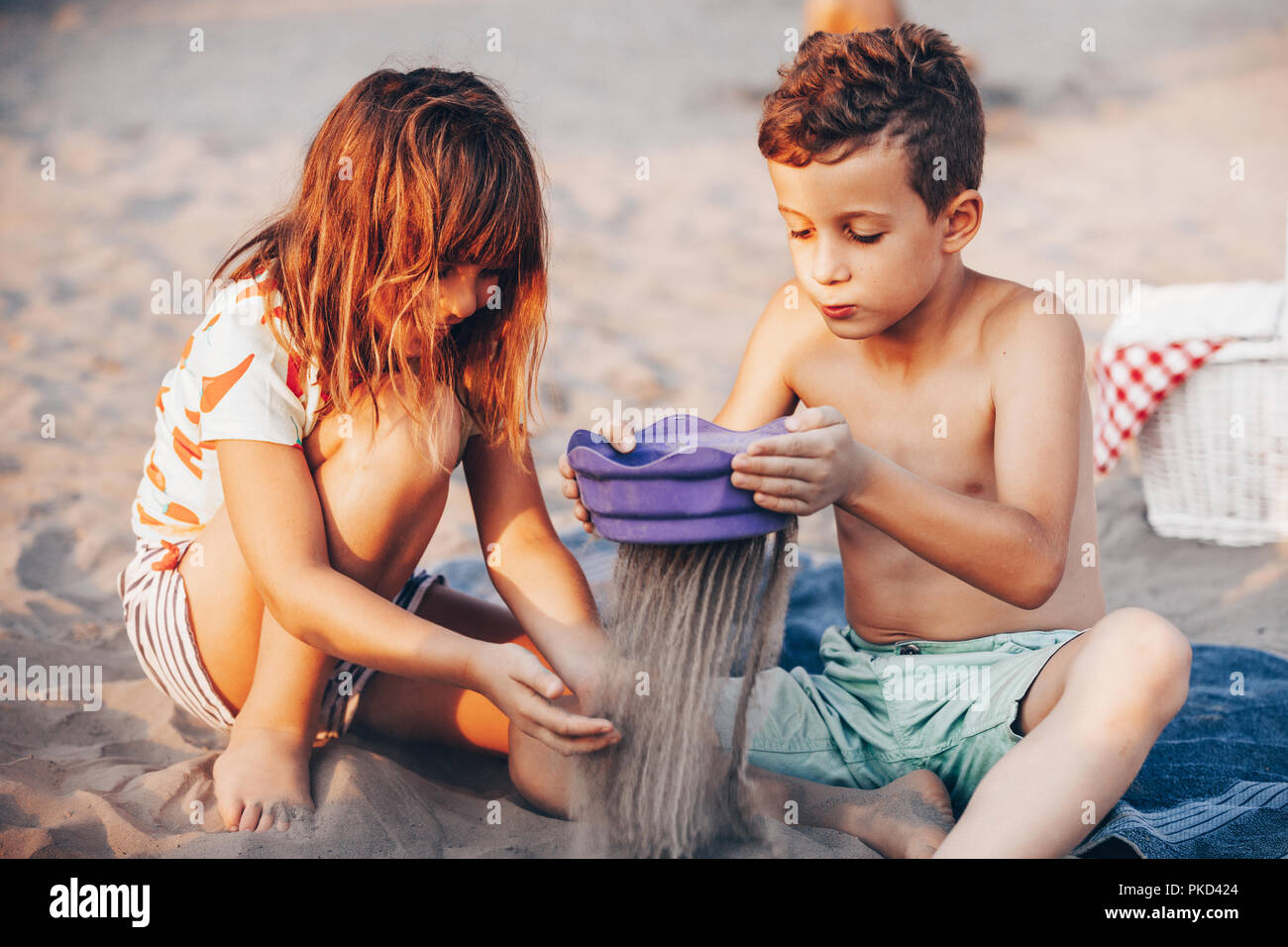 Happy positive children sitting on a towel on the beach and playing with sand. Summer vacation and healthy lifestyle concept - Stock Image