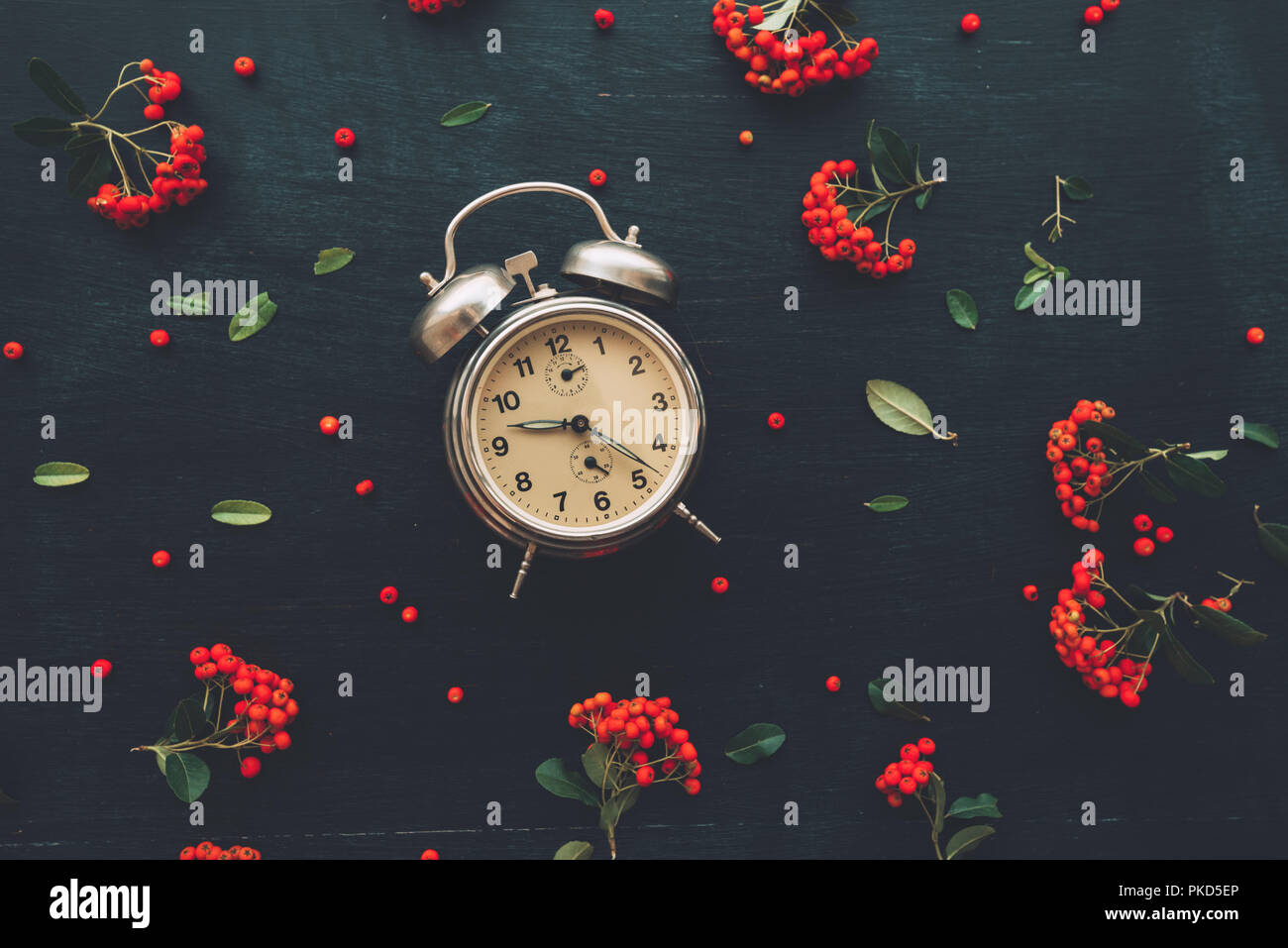Flat lay vintage alarm clock on dark black background, top view minimal composition with retro floral arrangement Stock Photo