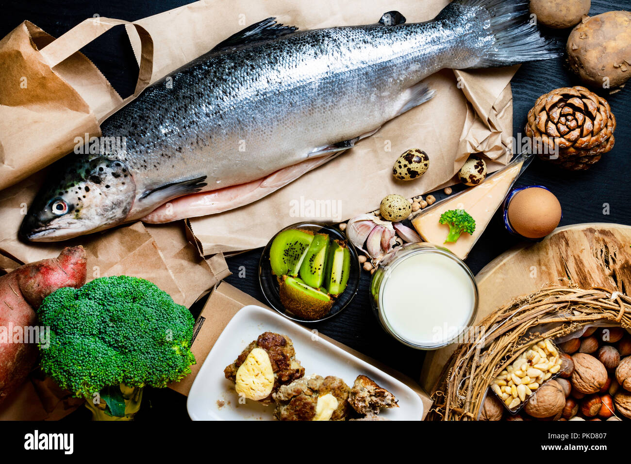 Products containing phosphorus salmon fish, pine nuts, peanuts, anchovy, cheese, milk, eggs, broccoli, kiwi, potatoes, meat, beans garlic on a round cutting board and black wooden background - Stock Image