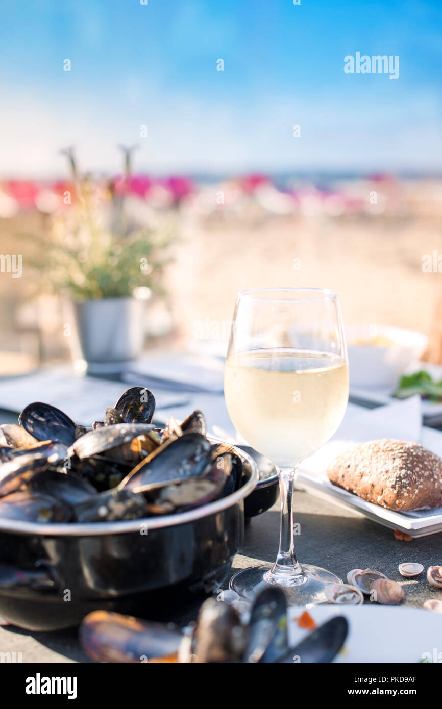 Mussels in a saucepan and a glass of cold white wine. Delicious seafood dinner in a restaurant on the beach. Copy space. - Stock Image