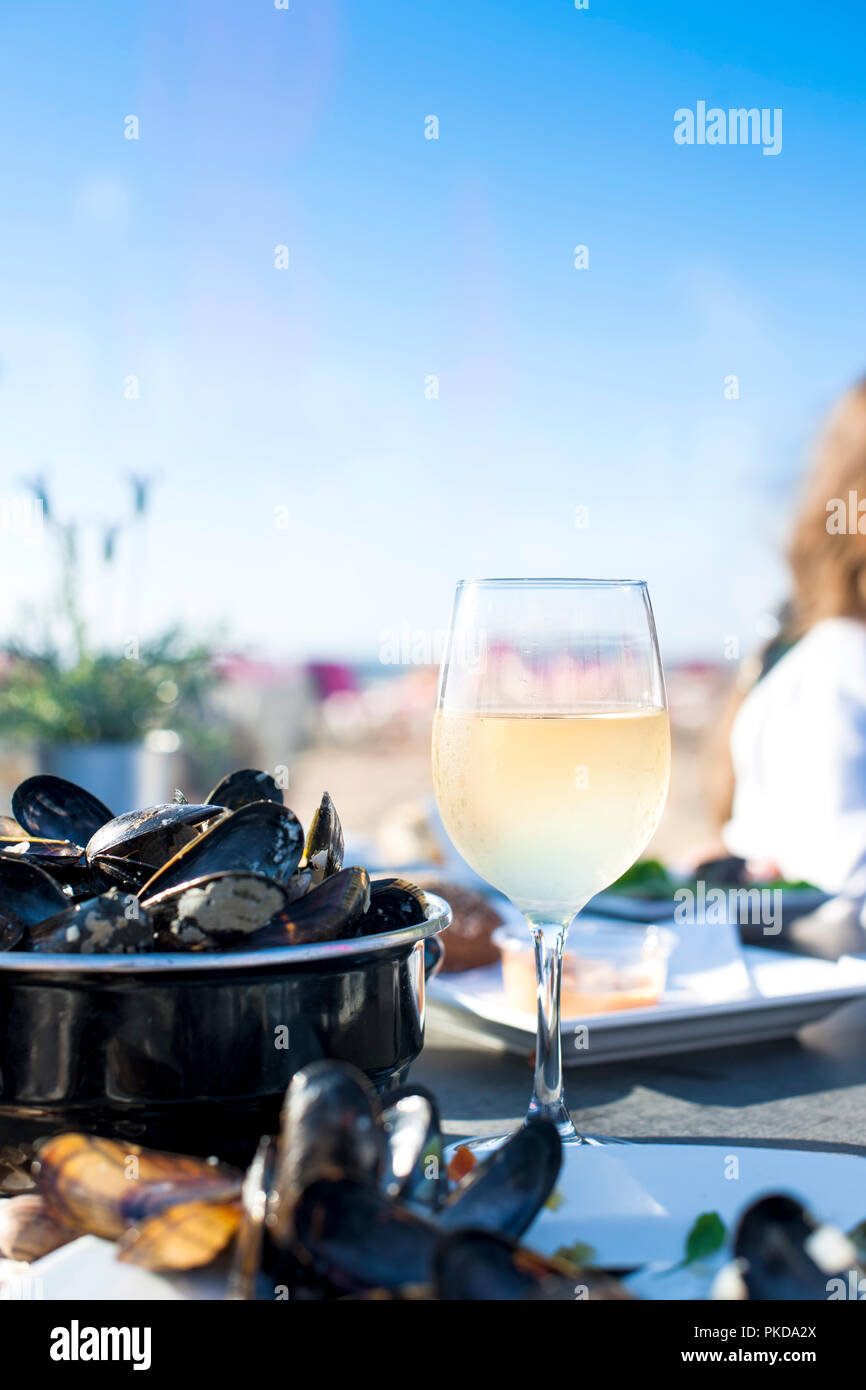 Mussels in a saucepan and a glass of cold white wine. Delicious seafood dinner in a restaurant on the beach. Copy space Stock Photo