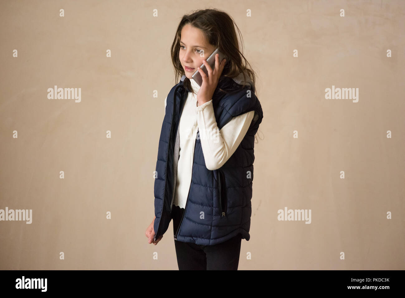 beautiful little girl in sleeveless jacket talking by cell phone - Stock Image
