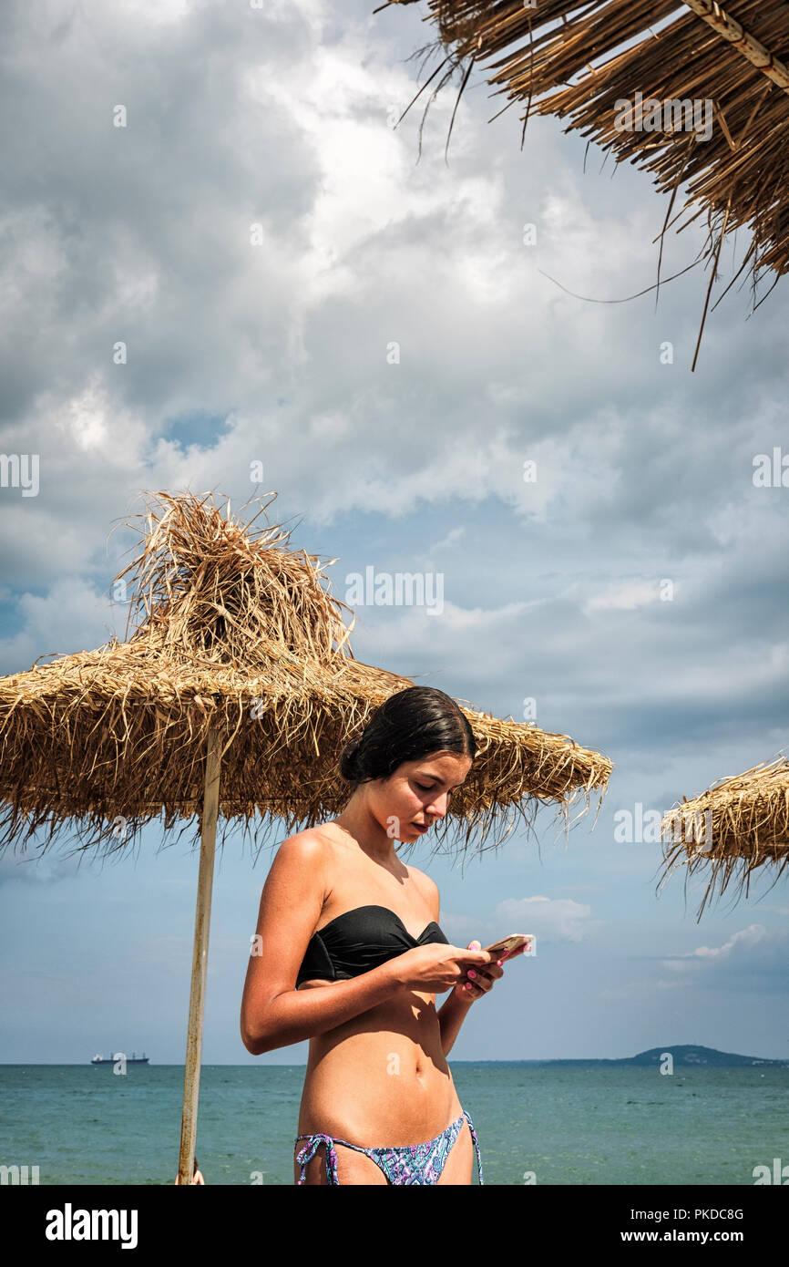 Teenage girl  in bikini looking at her phone on the beach - Stock Image