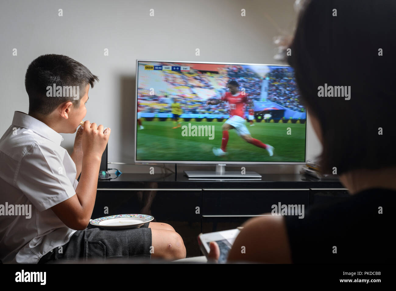 Schoolboy 10 years old,in school uniform snacking and watching football match on TV - Stock Image
