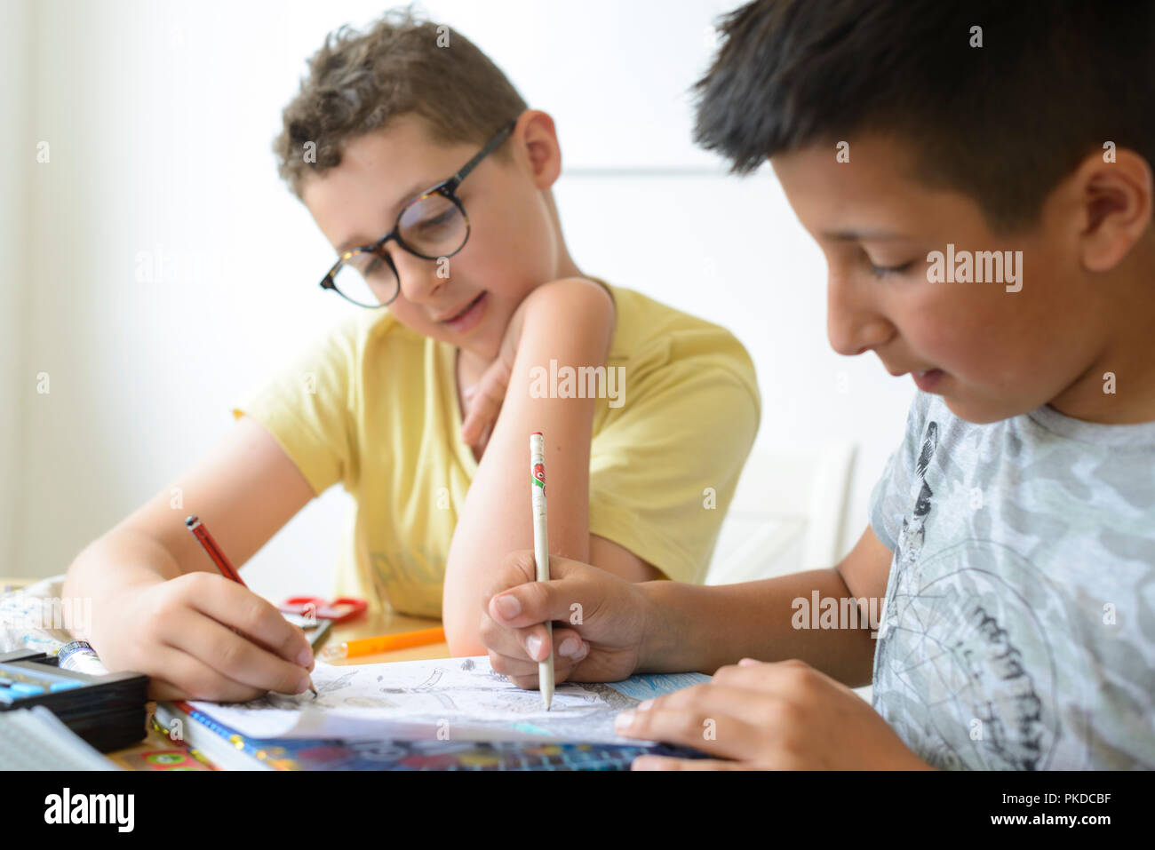 UK- Boy helps his schoolmate with maths homework - Stock Image