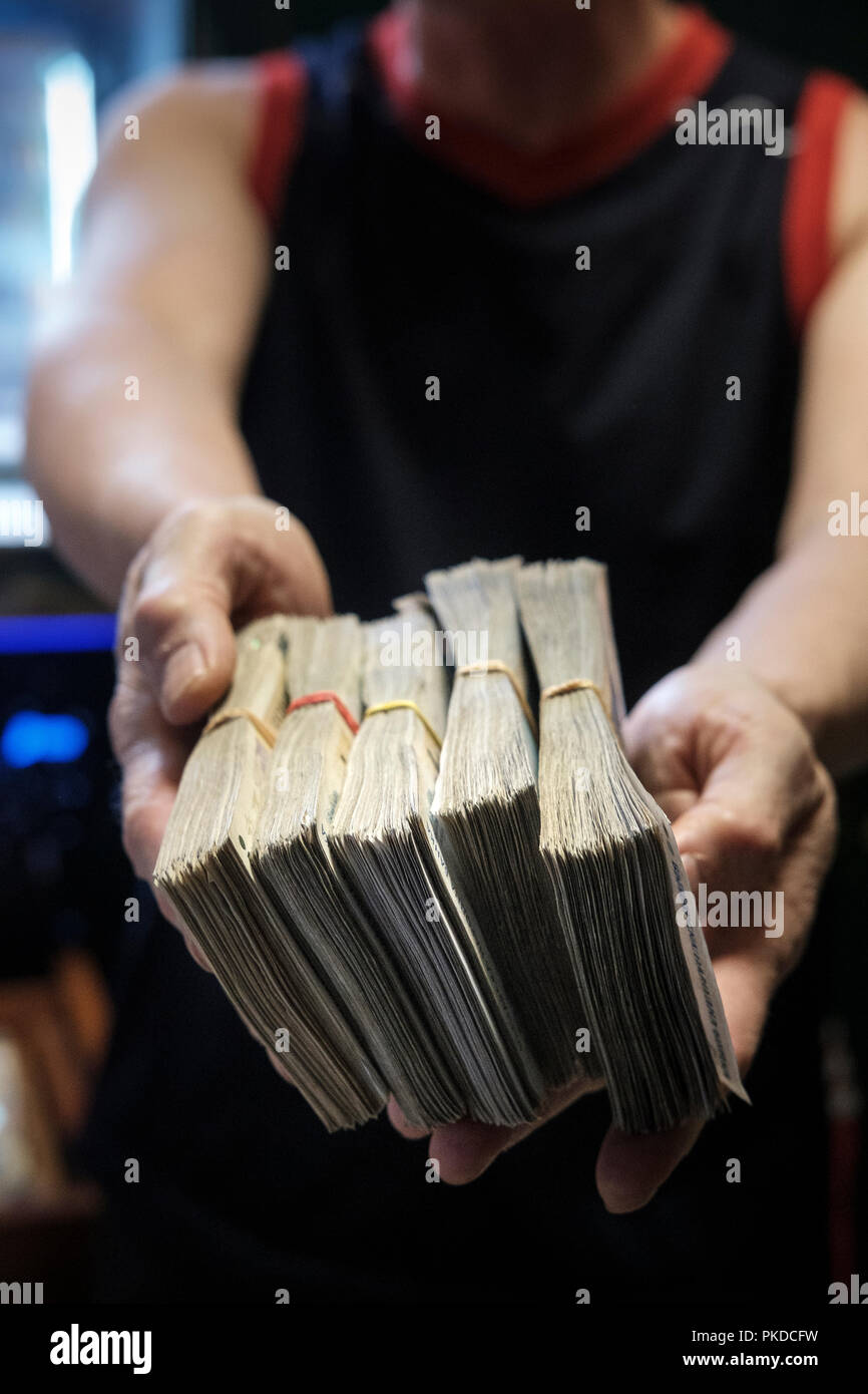 Person holding a stash of money.Corruption concept- cash,dirty money,money laundry - Stock Image
