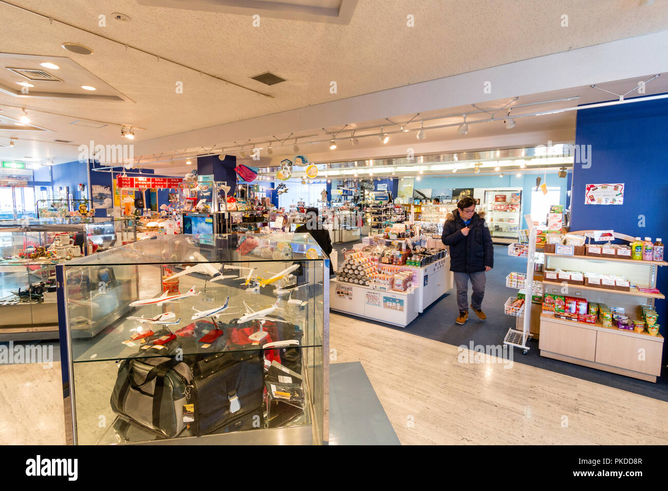 Japan, Osaka. Kansai International Airport. KIX. Interior, Sky Museum shop. General view of display counters, models and products with two customer. - Stock Image