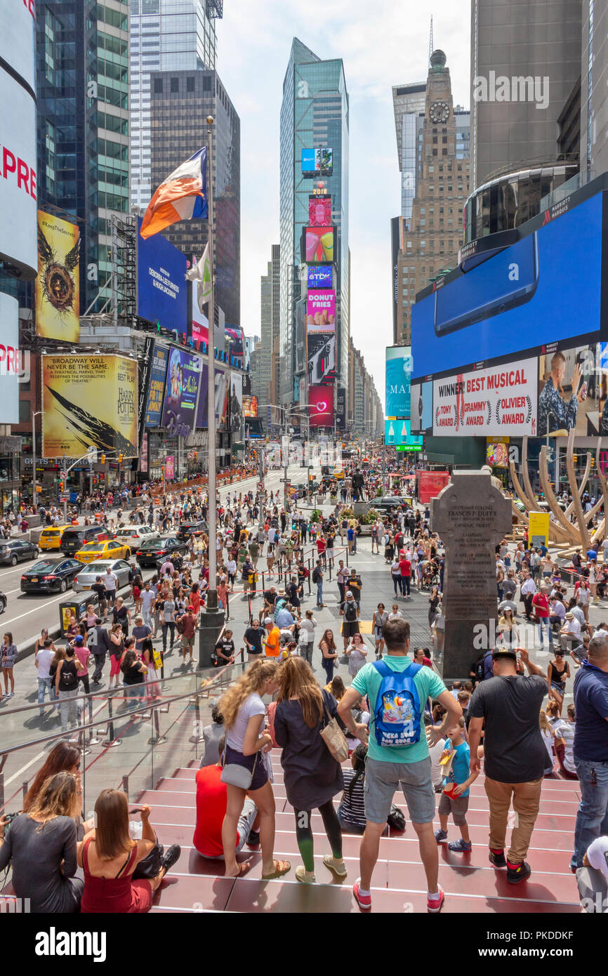 Visitors and tourists enjoying themselves at Times Square, 42nd Street in Manhattan, New York City. - Stock Image