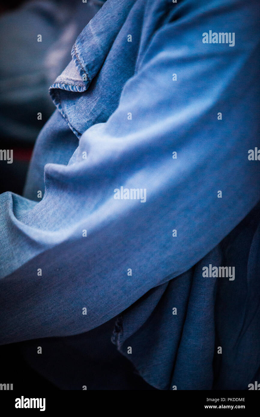 Close up/ full frame of a woman wearing a daed blue denim shirt / blouse / top with a focus on the arm and draped neckline - Stock Image