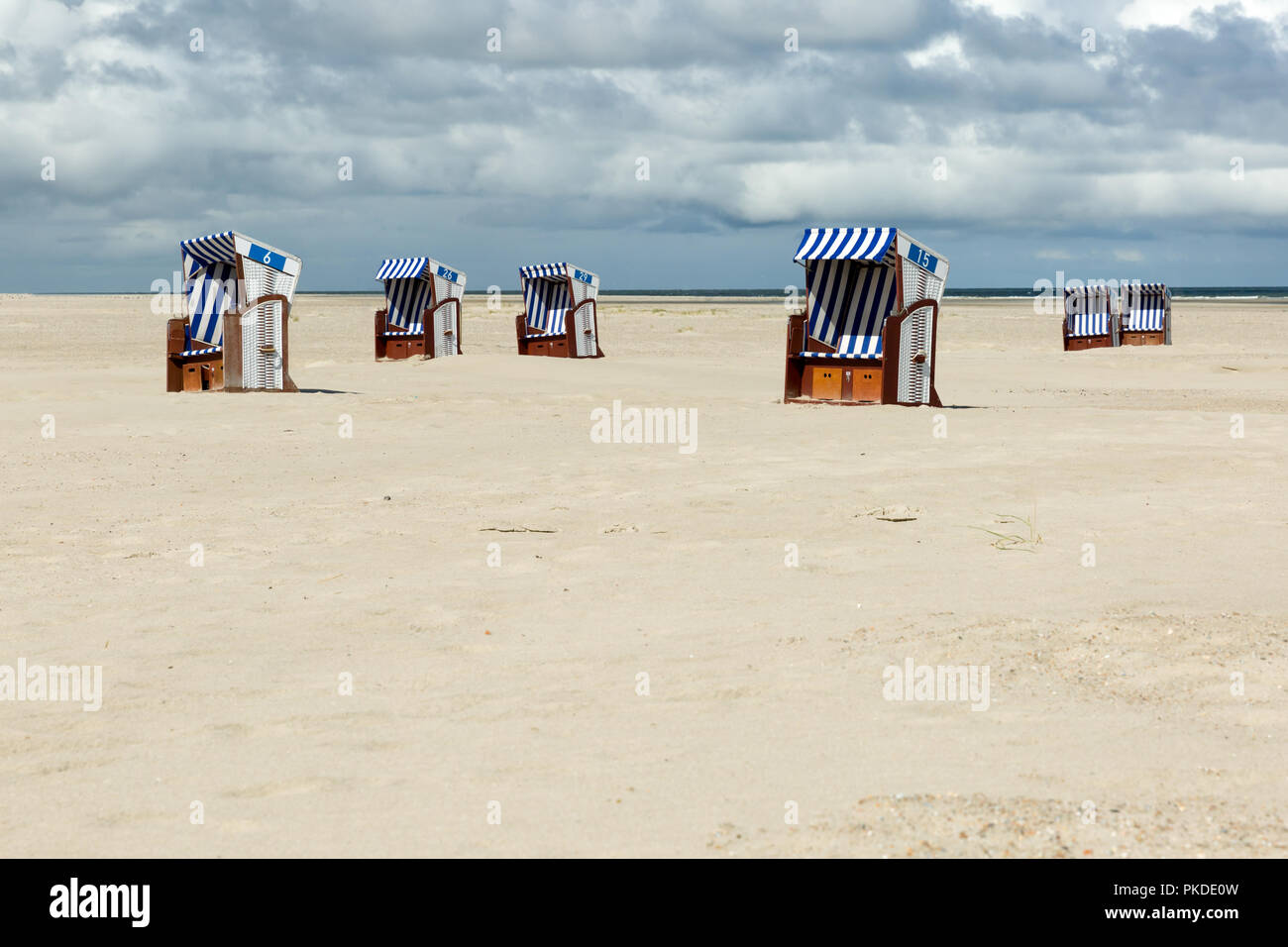 Roofed wicker beach chairs at the coastline of the German island Norderney in front of the ocean. Wide angle view Stock Photo