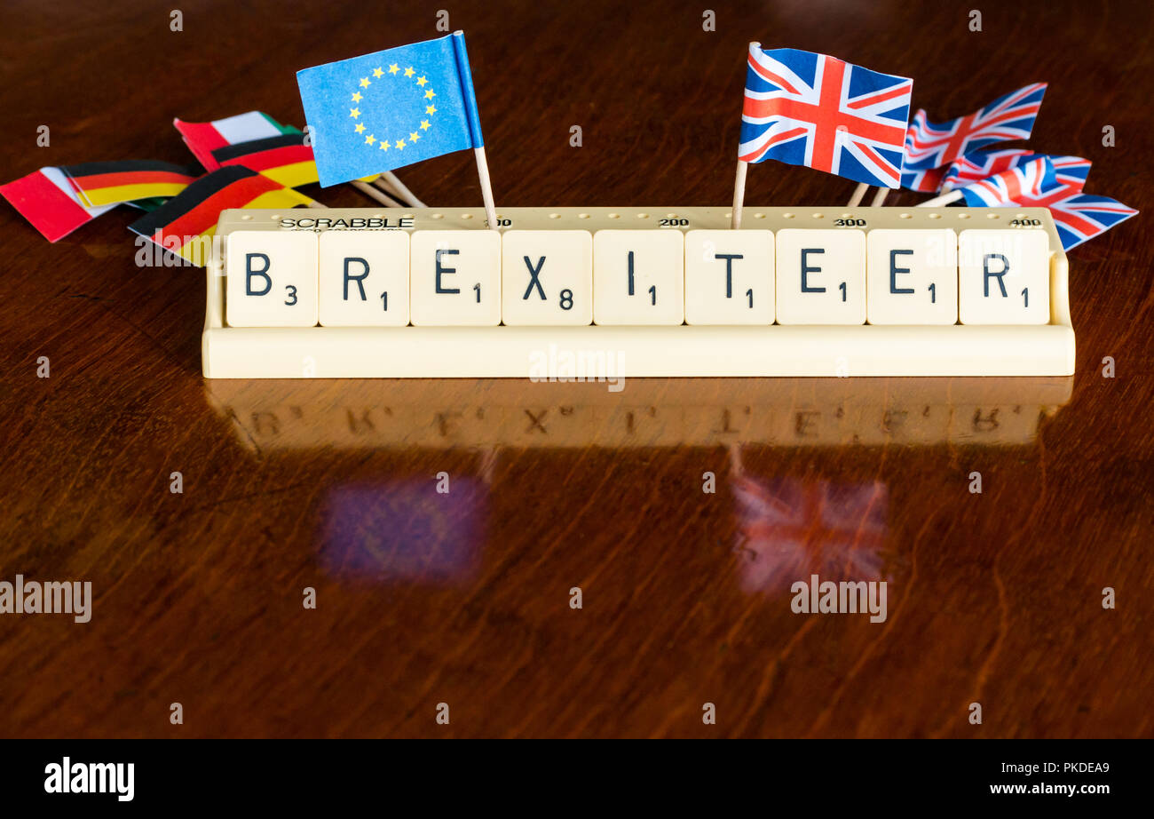 Scrabble letters spelling Brexiteer in Scrabble tray with British Union Jack European Union and Germany flags on dark mahogany background - Stock Image